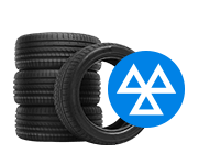 Stack of tyres next to a white MOT sign inside a blue circle.
