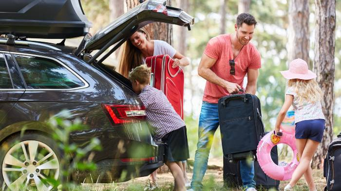 A family packing their suitcases into their hire car