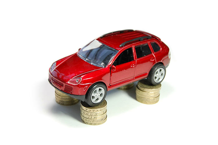 Red toy car stacked on pound coins