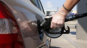 Hand in a disposable glove holding a fuel pump to fill up car