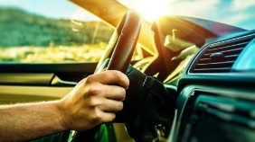 A close up of a hand on a steering wheel with the sun setting in the back ground
