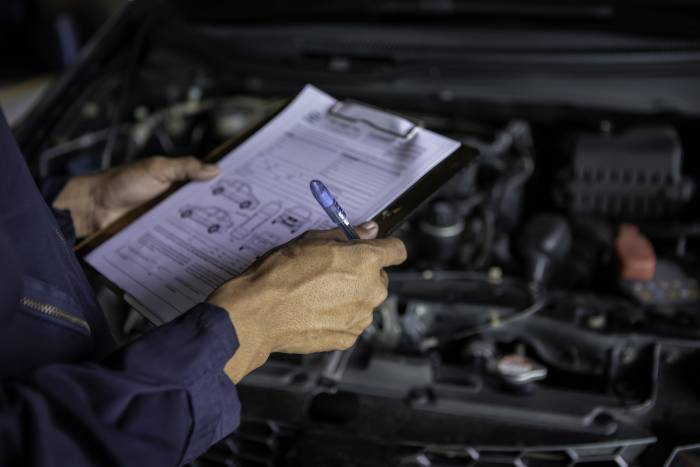 A mechanic ticking off a car service checklist