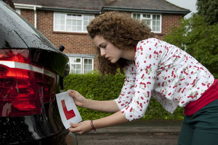 A young girl attaching her learner plate onto the back of a car