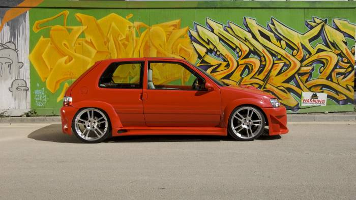 A red modified car infront of a wall of graphiti