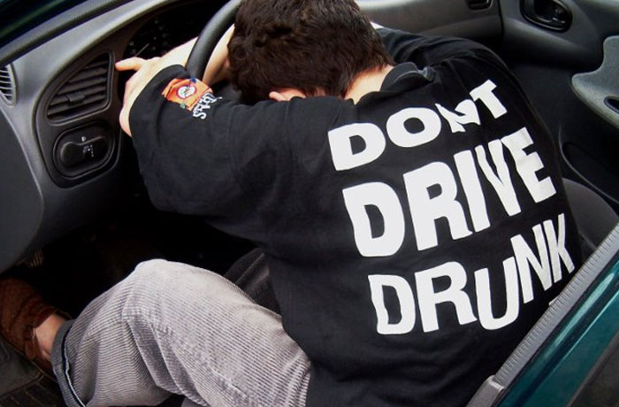 Man an asleep at wheel wearing 'Don't drive drunk' shirt