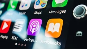 A close up of an in-car media system and the podcasts app icon