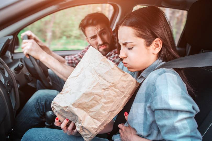 Two people in car and the passenger is being sick into a brown bag