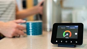 Smart meter on kitchen counter with kettle and mug in background.