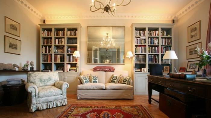A grand lounge with a writers desk and book cases