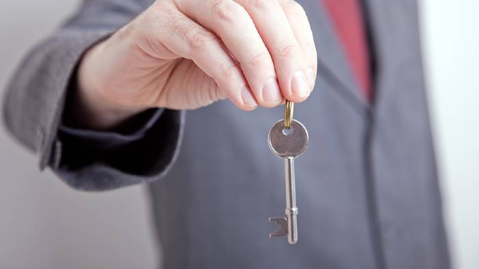 A man in a suit holding a key
