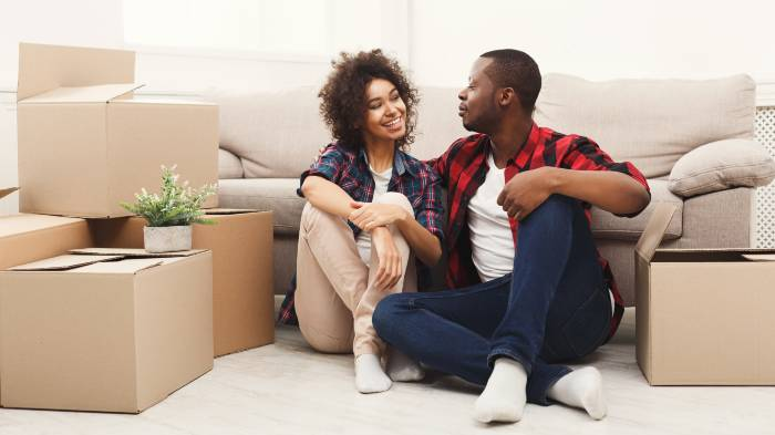 A happy couple sat on the floor in front of their sofa, surrounded by boxes