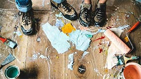 Spilled paint tins and brushes with two pairs of feet on the floor.