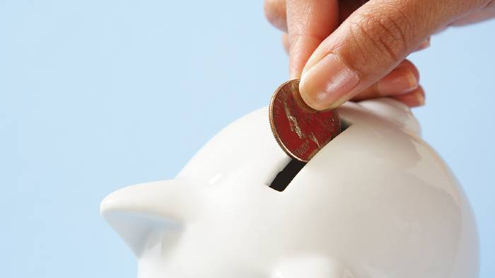 A hand holding a coin, putting it into a white piggy bank with a blue background