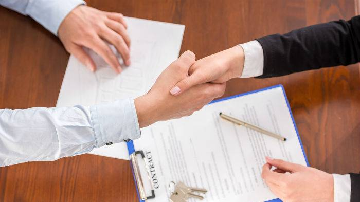 Two people shaking hands over paperwork and keys