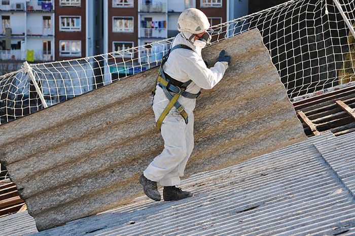 Someone wearing protective equipment carrying a sheet of asbestos roofing