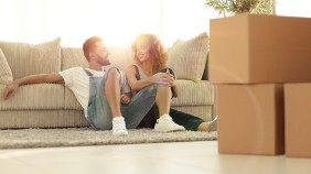 A young couple sitting on the floor in front of their sofa surrounded by boxes