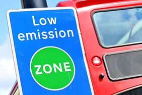 Low emission zone sign in front of a red bus