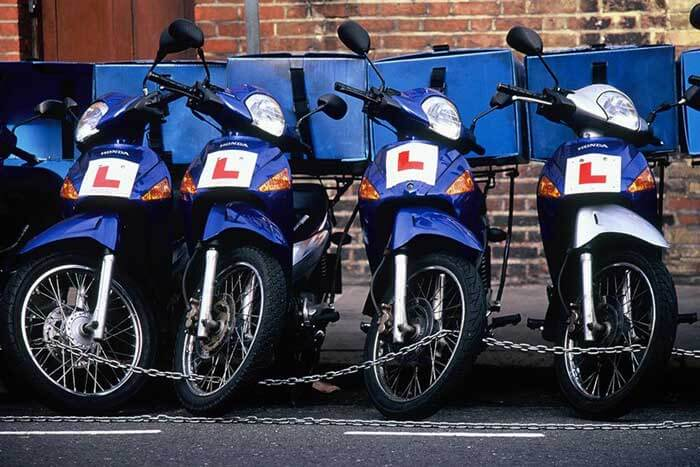 Four blue scooters chained up in a row with L plates on them