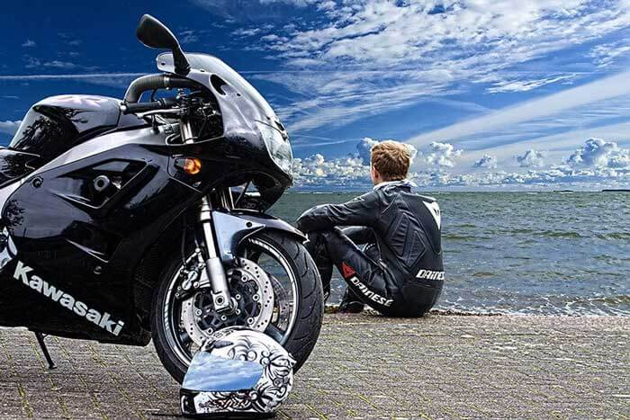 Black Kawasaki motorbike with rider in the background looking out to sea