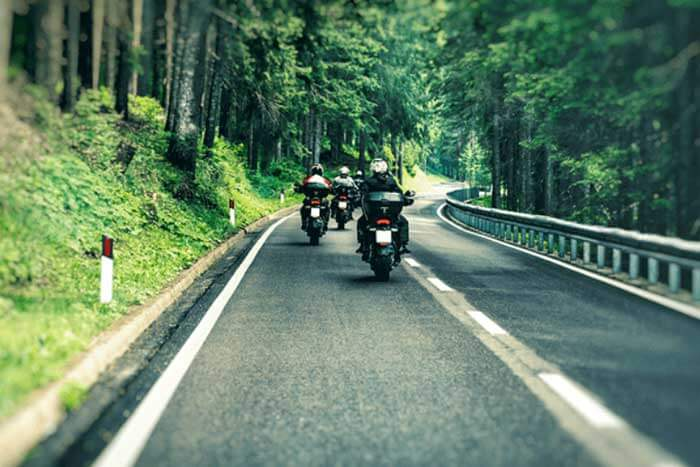 A group of bikers riding down the road