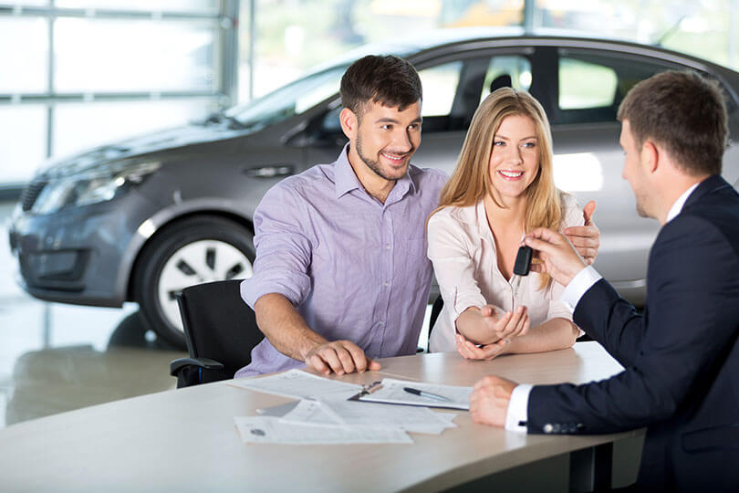 Couple at a car showroom getting car finance
