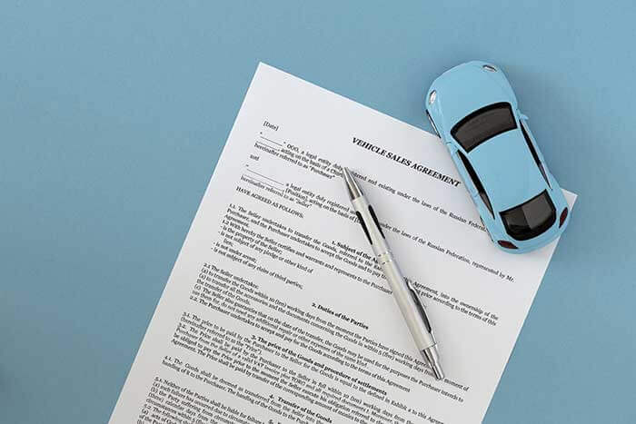 Vehicle sales agreement, a pen and a toy car