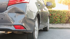 A car with a dent in the rear bumper caused by an untraceable driver