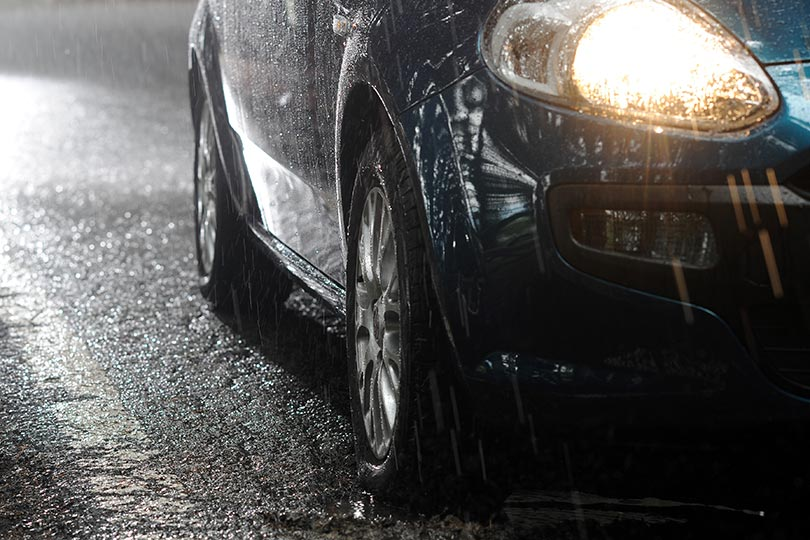 A car stopped on the road with its headlights on during a heavy rain.