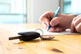 signing paper with car key on table