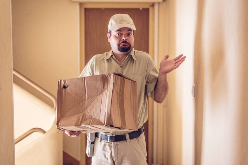 A delivery man with a smashed up cardboard box