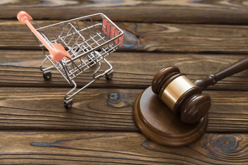 A miniature shopping trolley with a judges gavel