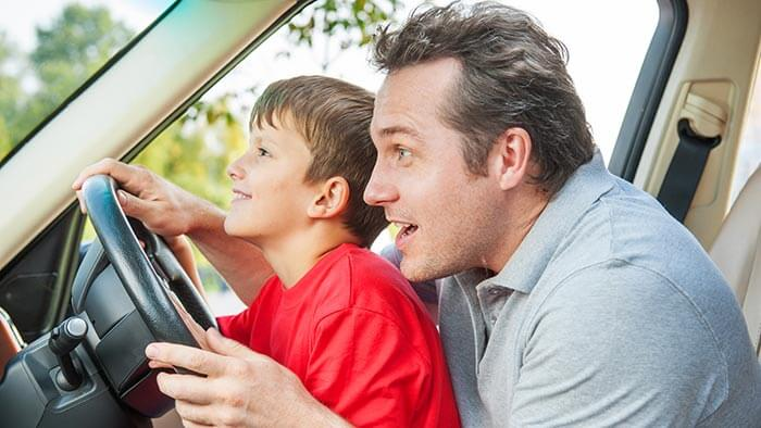 Father in car teaching son how to drive