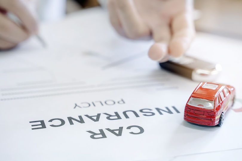 Car insurance paperwork being signed with a red toy car on the desk