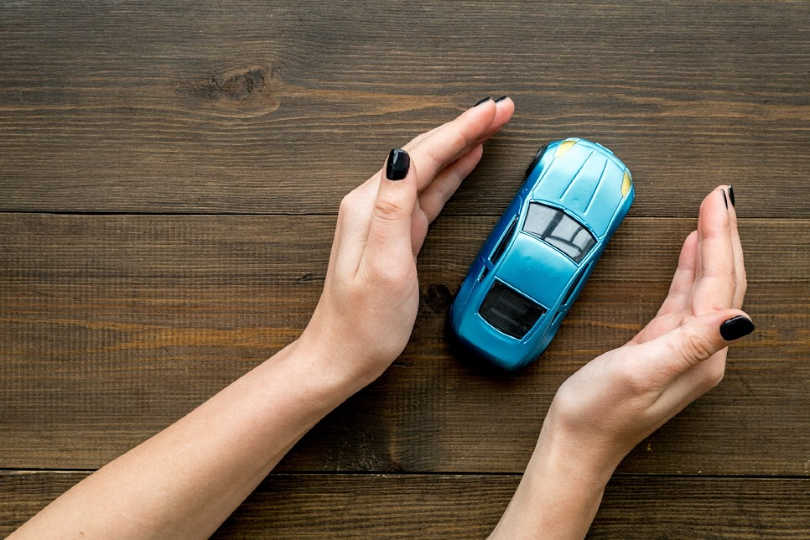 Hands surrounding a toy car to protect it