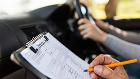 A learner driver taking their test while their instructor writes on a clipboarda