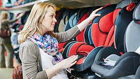 Pregnant woman looking at child car seats