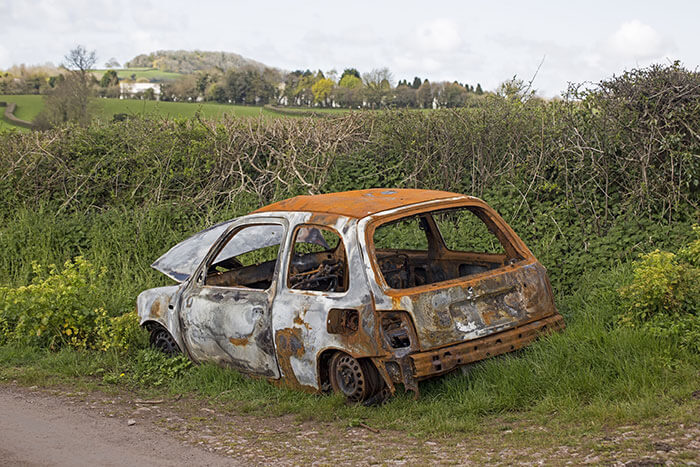 A rusted, abandoned car left on the side of the road next to a field