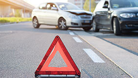 A red warning triangle in the foreground with a road traffic accident in the background