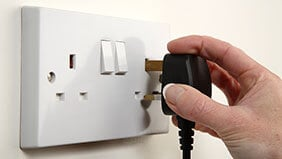 Hand unplugging a plug from the wall