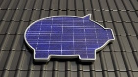 Money bank pig as solar panel on roof