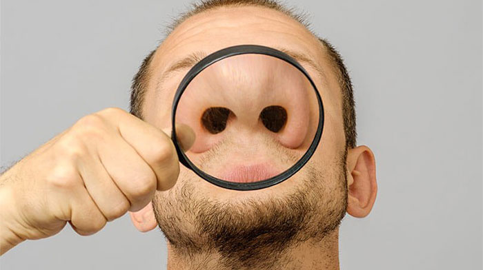 Man holding a magnifying glass up to his nose