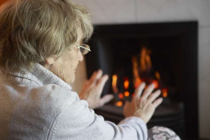 Older lady warming her hands by the fire