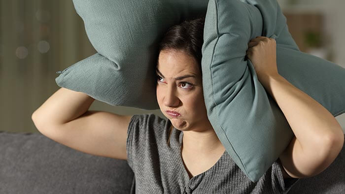 Angry woman with pillows over her ears