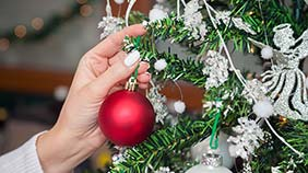 Red bauble being hung on a tree