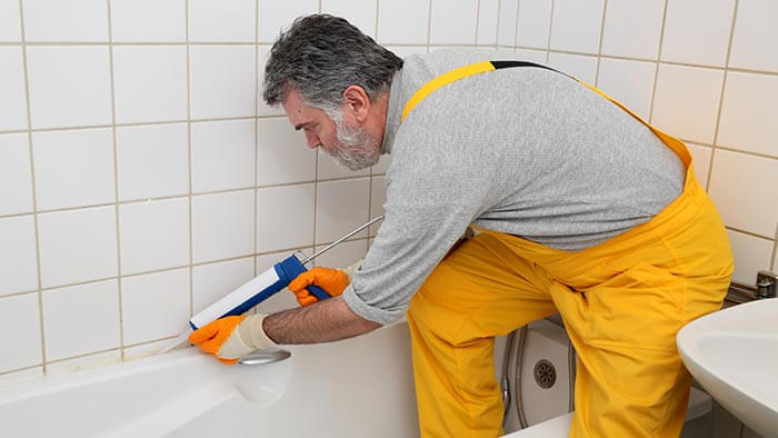 Bearded man resealing a bath with a sealant gun while wearing yellow overalls