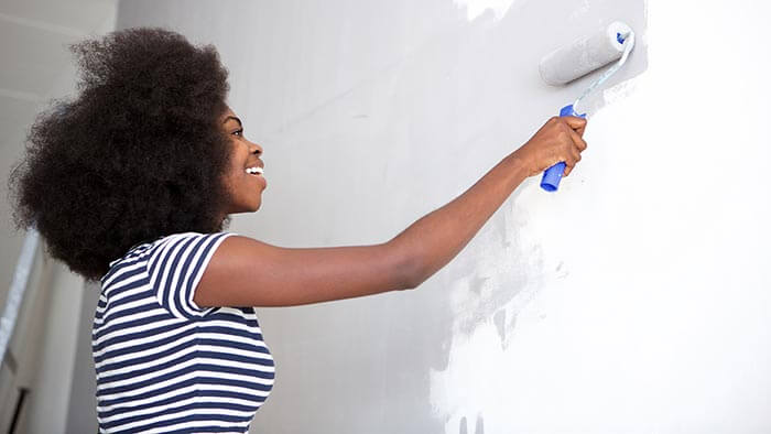 Woman painting an office wall with a paint roller