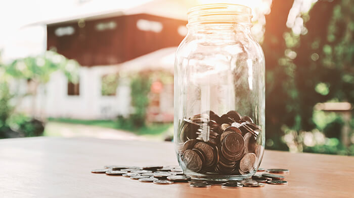 savings jar in front of a house