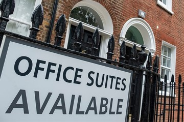 A sign outside a building with 'office suites available' written on it