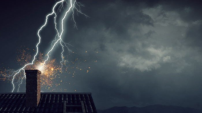 Lightning striking a home's chimney stack during a storm