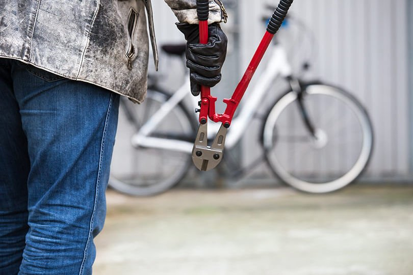 Thief holding a pair of bolt cutters with a bicycle in the background